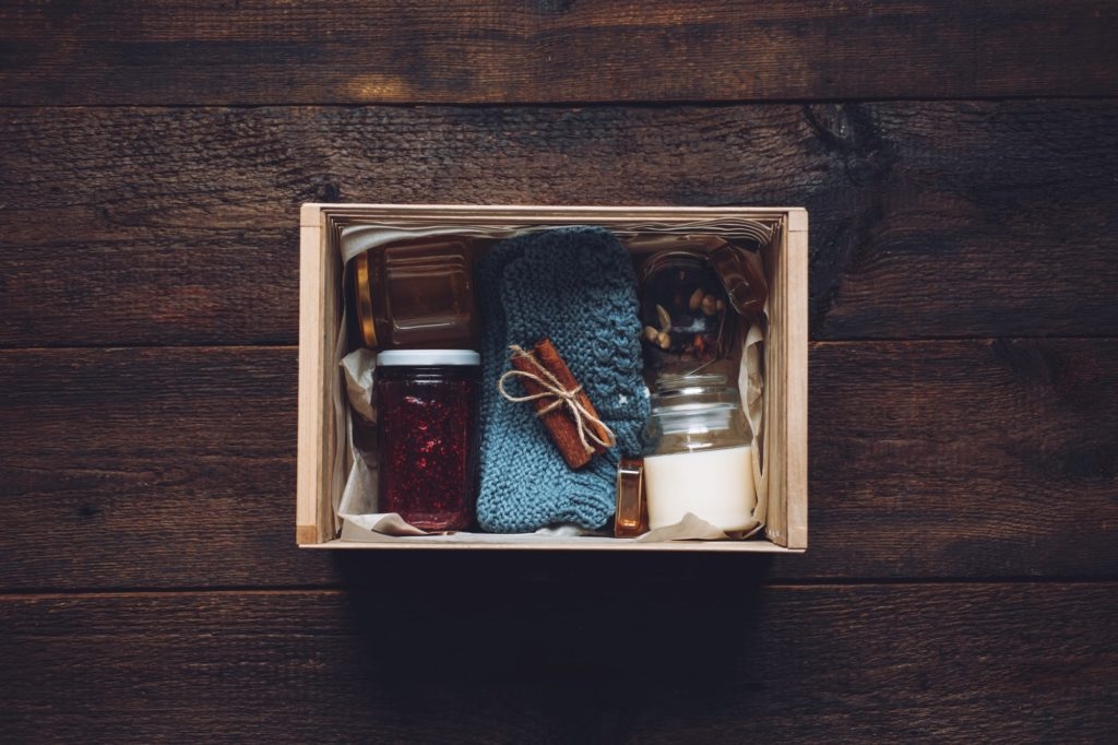 Care box, package ideas. Fall or Winter care box with sweets and warm clothes. Care Package Delivery